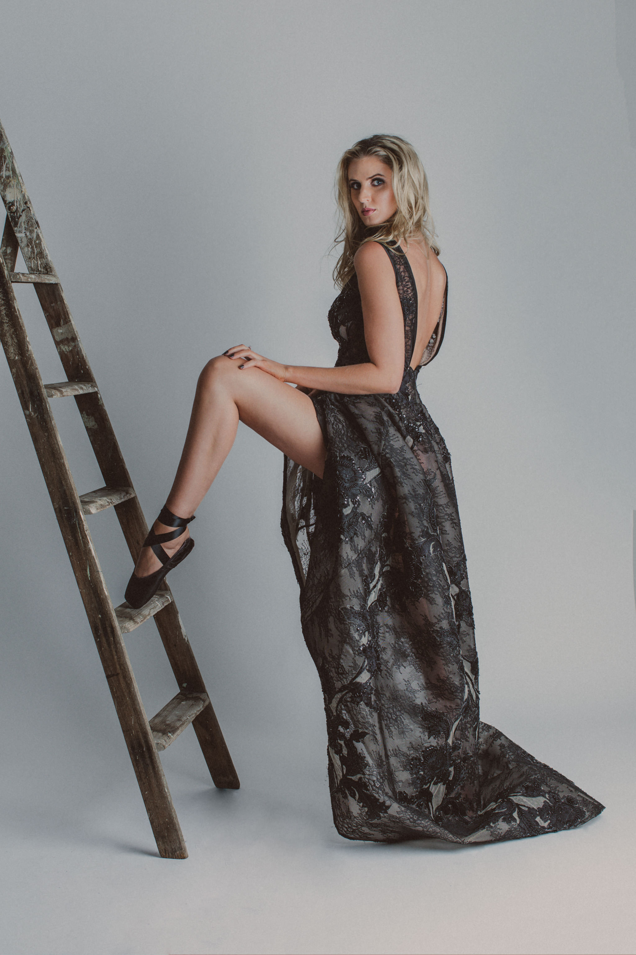 creative studio photographer - girl on ladder in black dress