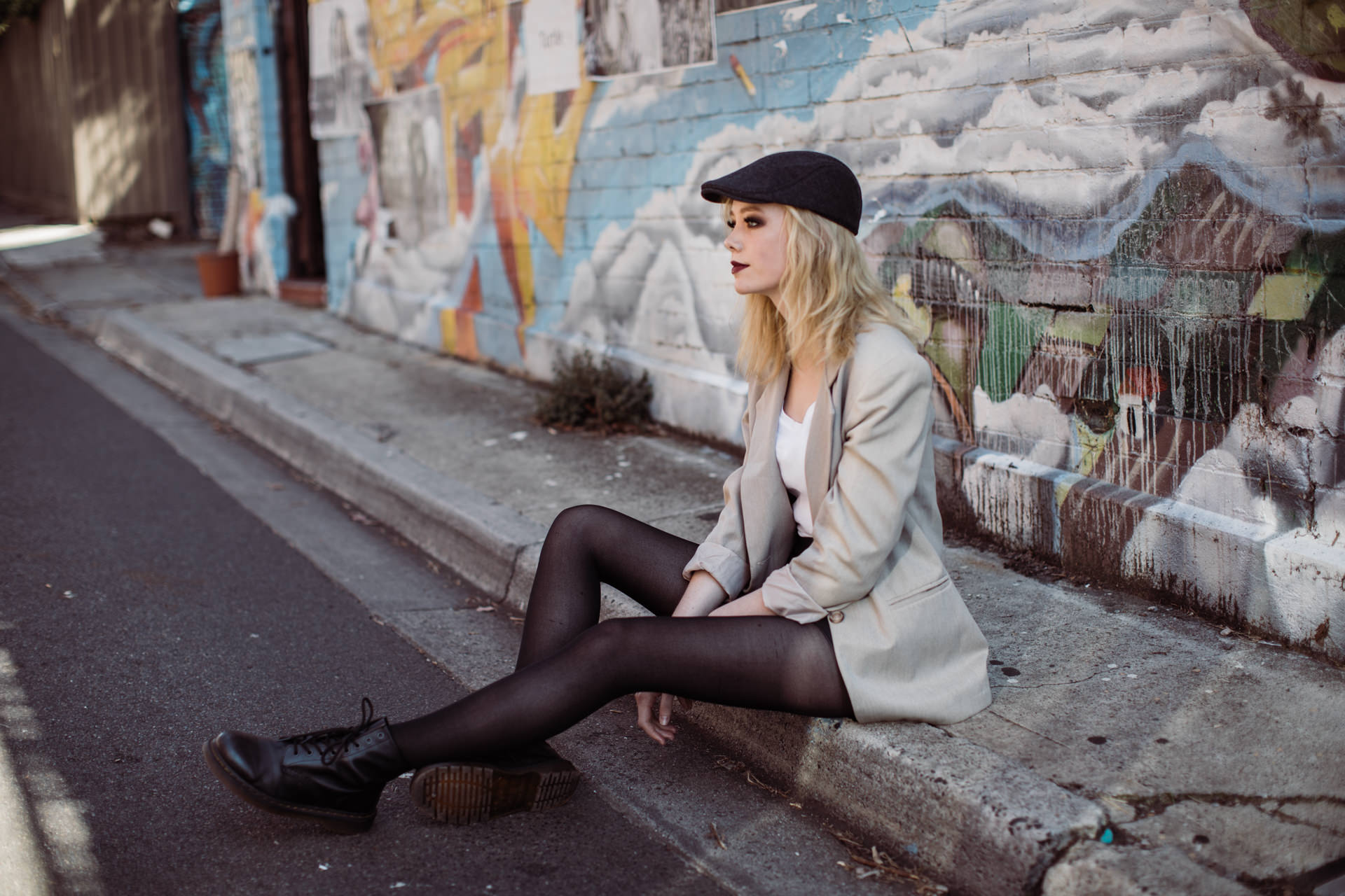 pretty girl sitting on street infront of street art in melbourne - advertising and commercial photography in melbourne