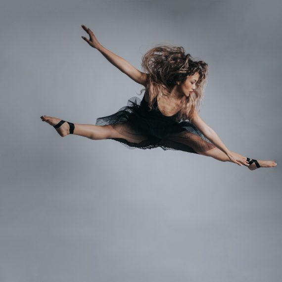 Dance action photography in Melbourne - Female dancer mid air in split jump in black dress - barefoot
