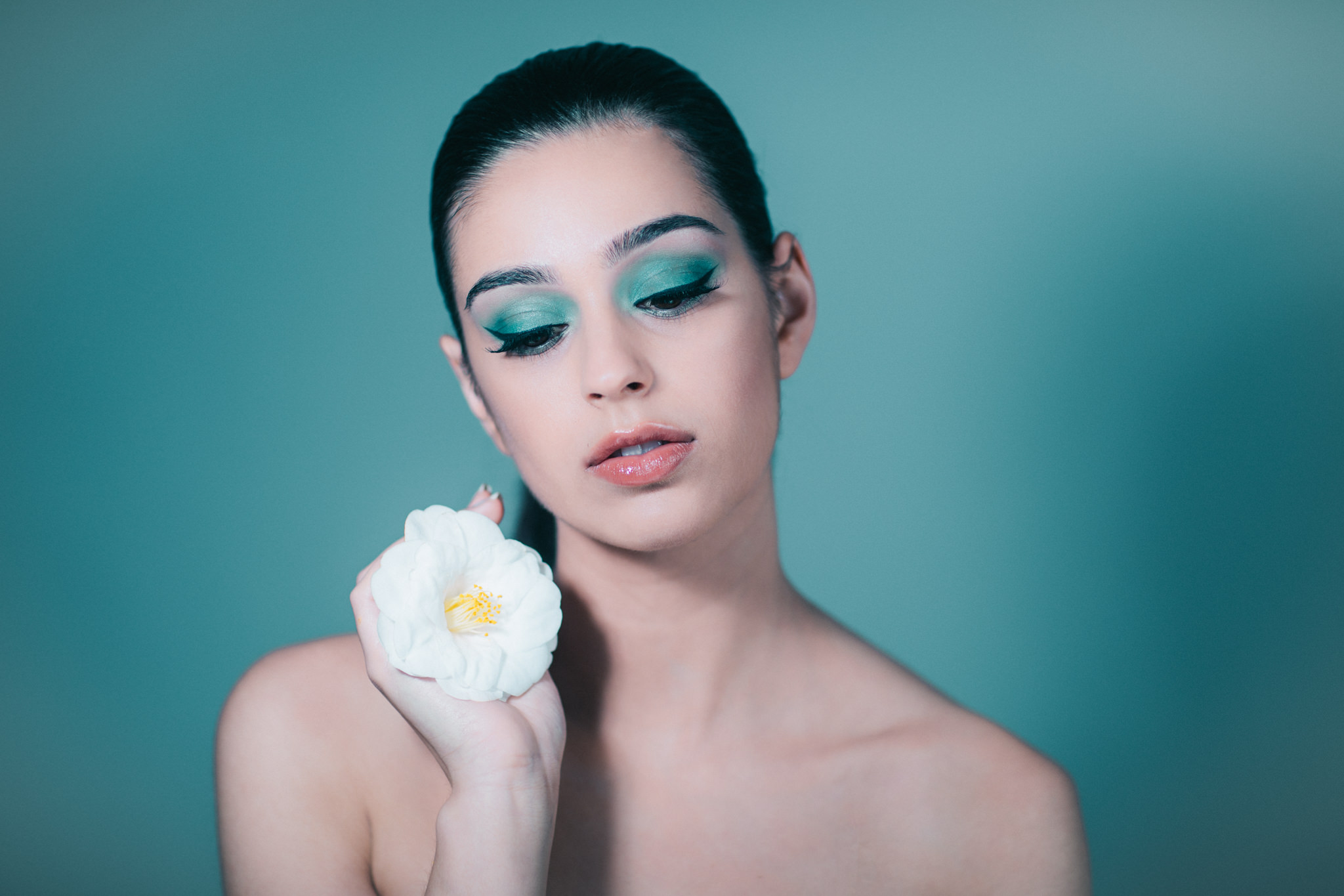beauty photos melbourne - model with flower (camelia) on blue backdrop